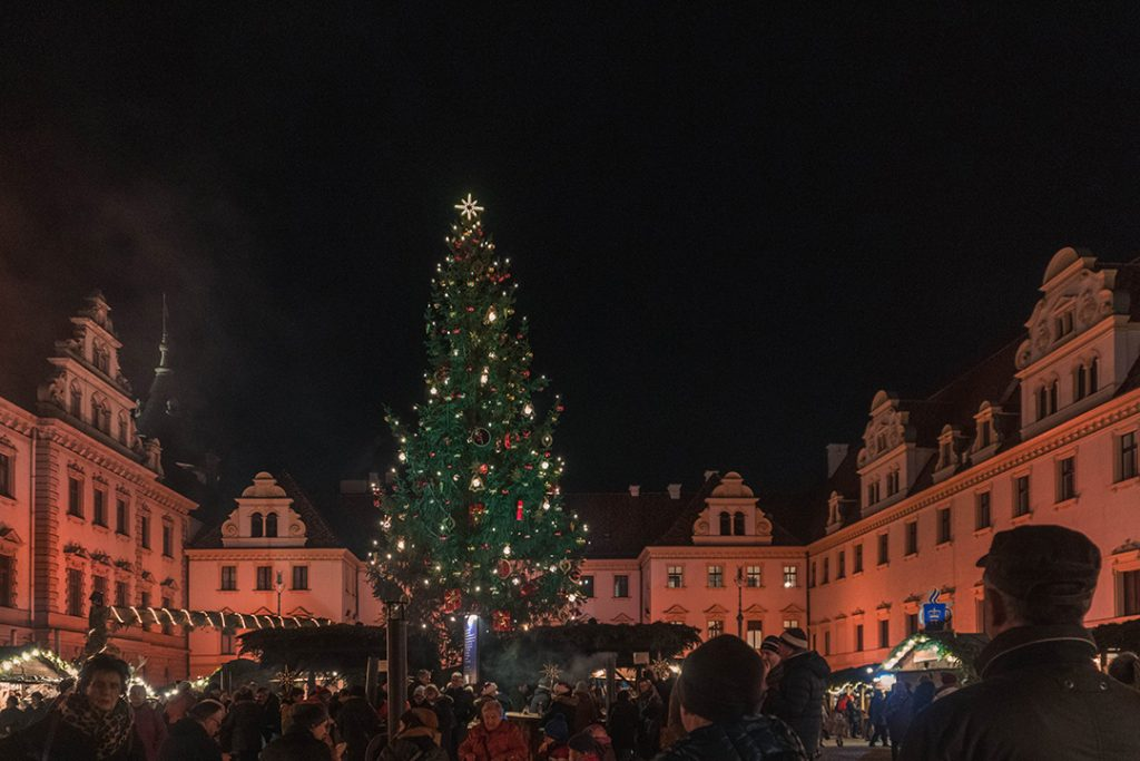 a huge christmas tree towers over small wooden booths in a castle courtyard