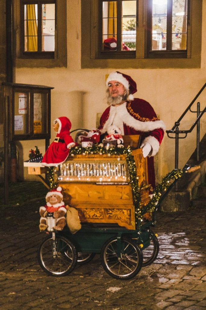 A man dressed as Santa Claus at a rolling machine which plays music