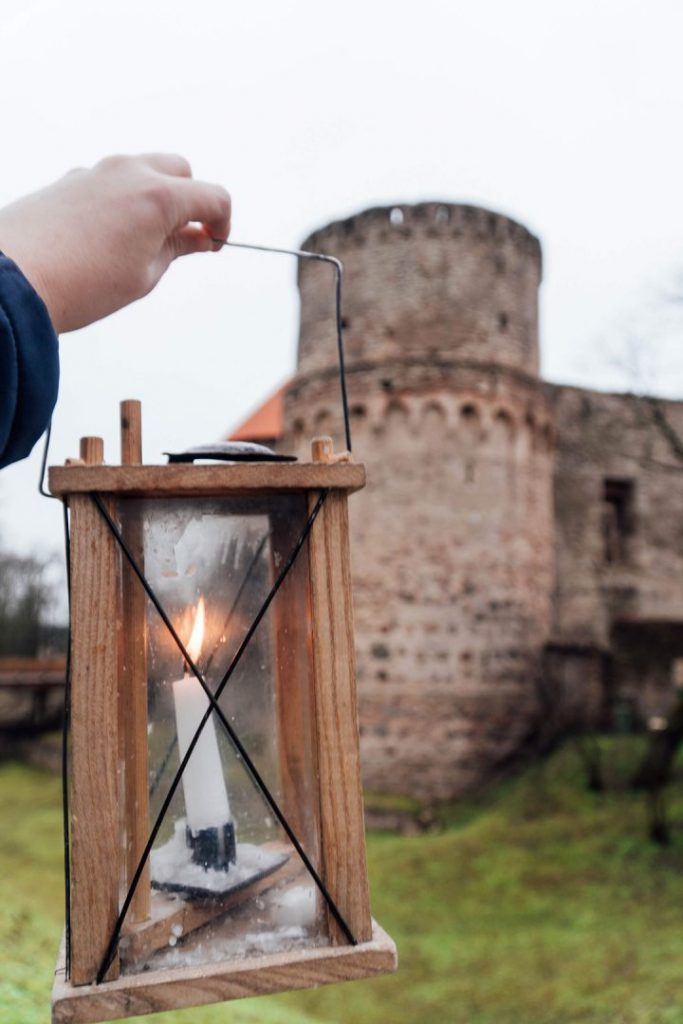a hand holding up an old timey lamp in front of a castle