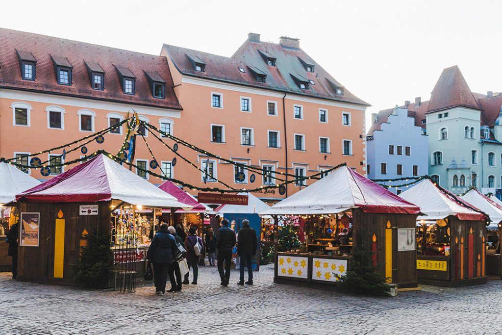 wooden booths with red roofs in a small square in Regensburg at the Lucrezia Market, one of the Regensburg Christmas Markets