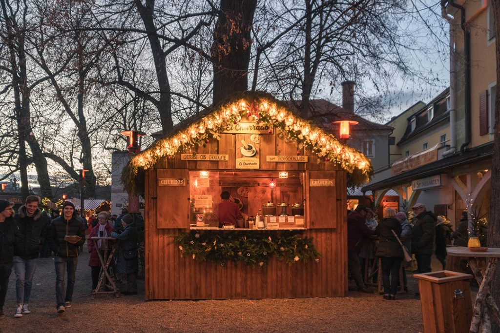 a small wooden booth with fairie lights trimming the roof at one of the regensburg christmas markets