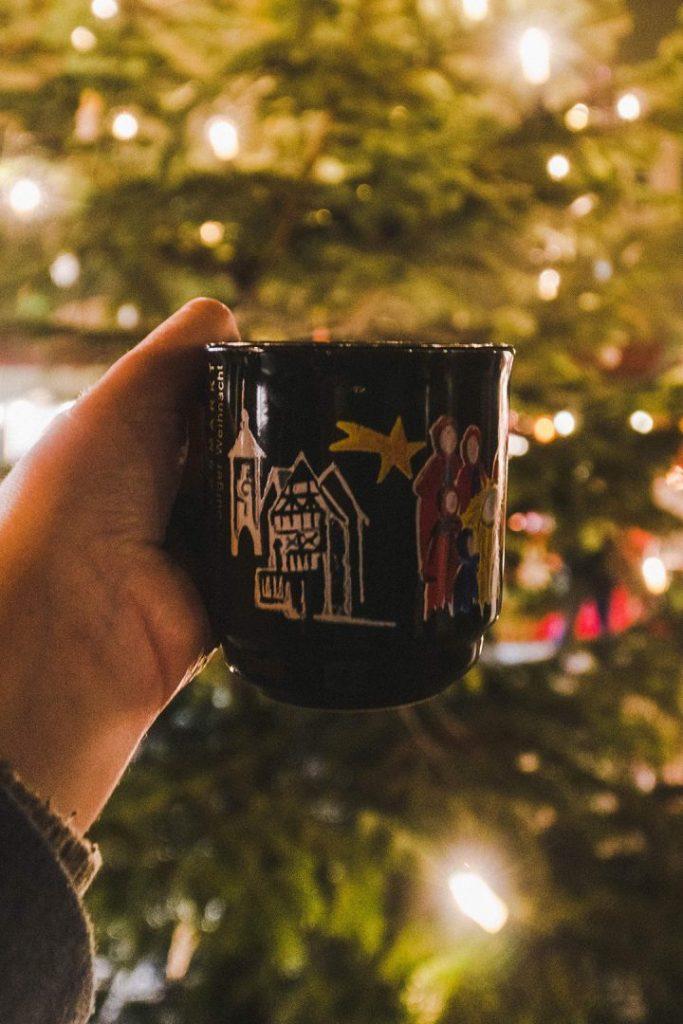 a hand holding up a gluhwein mug at the rothenburg ob der tauber christmas market