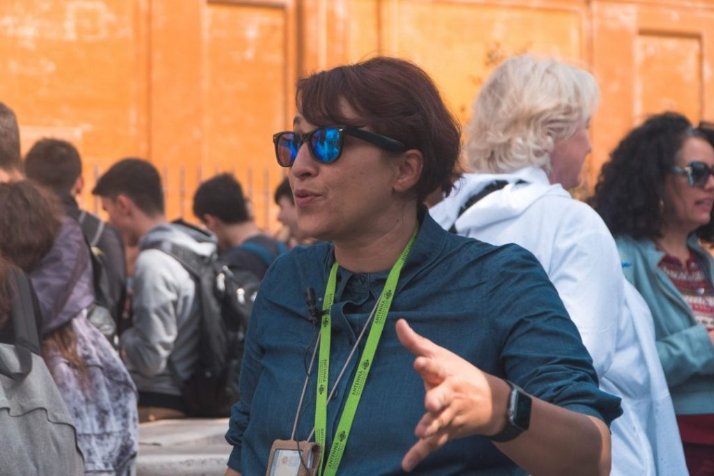 a female tour guide giving an explanation of something at the vatican