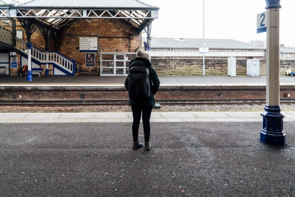 addie standing on a train platform wearing the nayosmart almight backpack