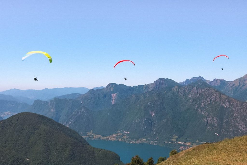 3 Paragliders in the air above Lake Idro in Valle del Chiese, Trentino, Italy