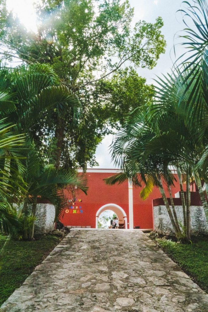 a red building - the entrance to cenote san lorenzo oxman, one of the valladolid cenotes