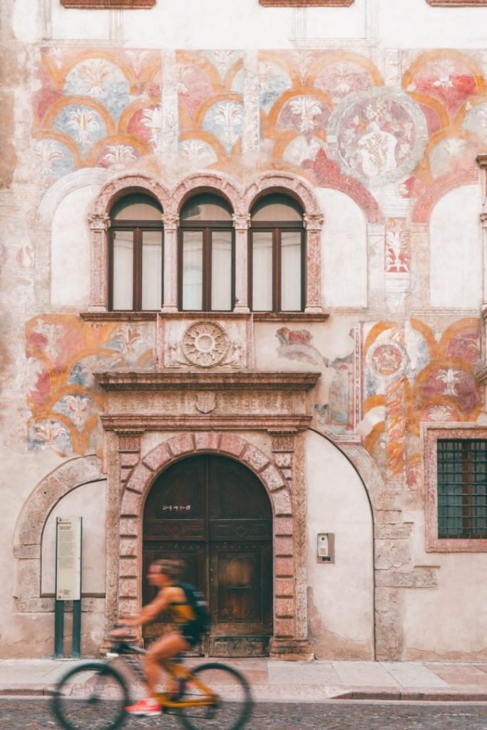 A woman on a bicycle riding past a frescoed fall in Trento, Italy