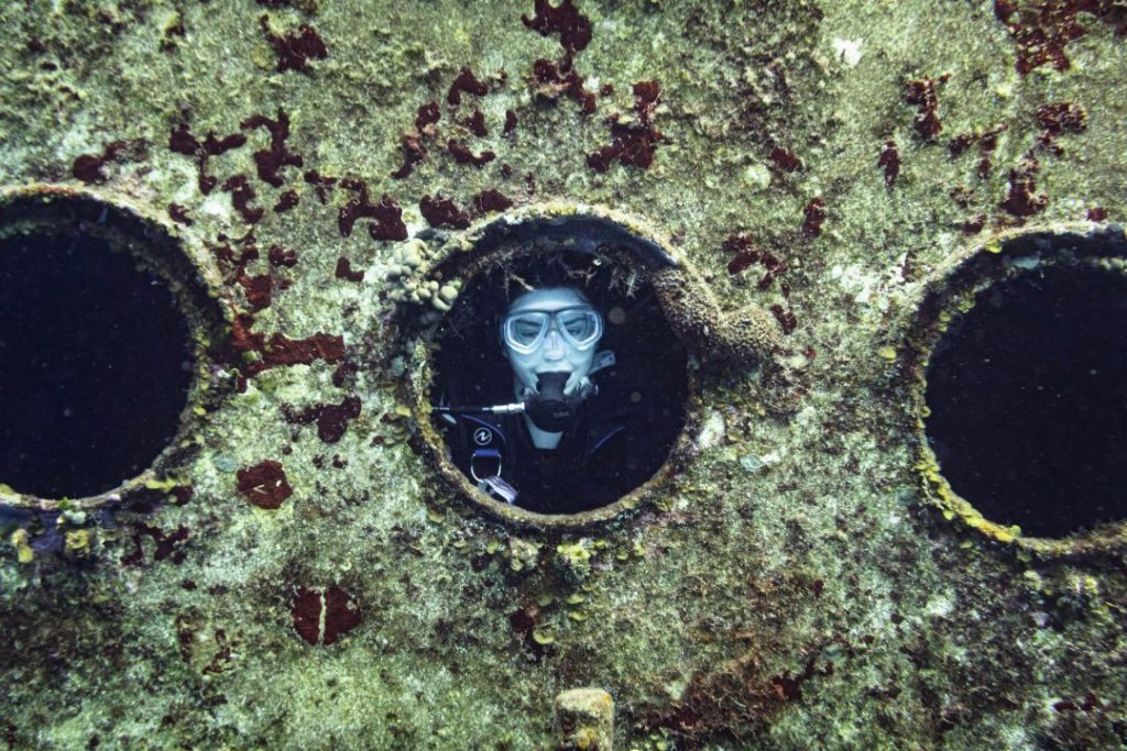 addie in full scuba gear peeking through the porthole of a shipwreck - cozumel scuba diving