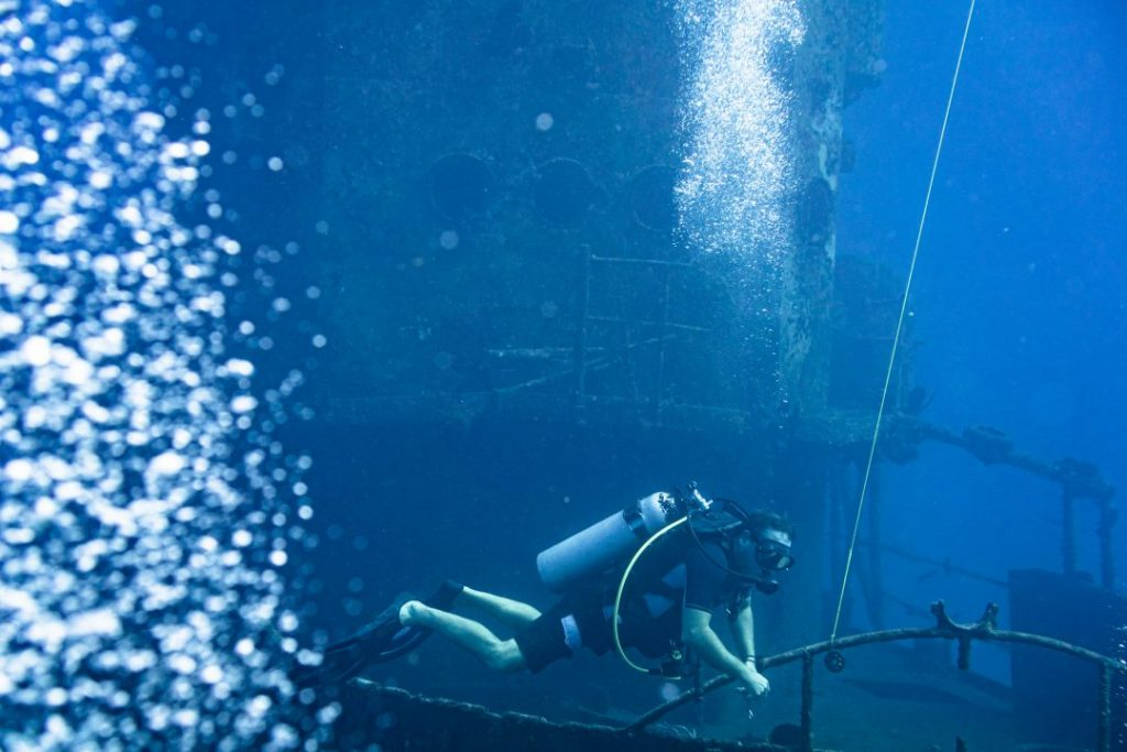 a scuba diver diving in front of a ship wreck
