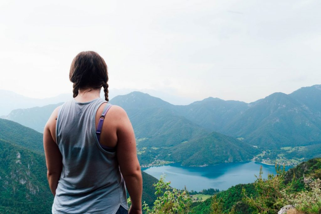 Girl in braids staring out at Valle di Ledro, Italy