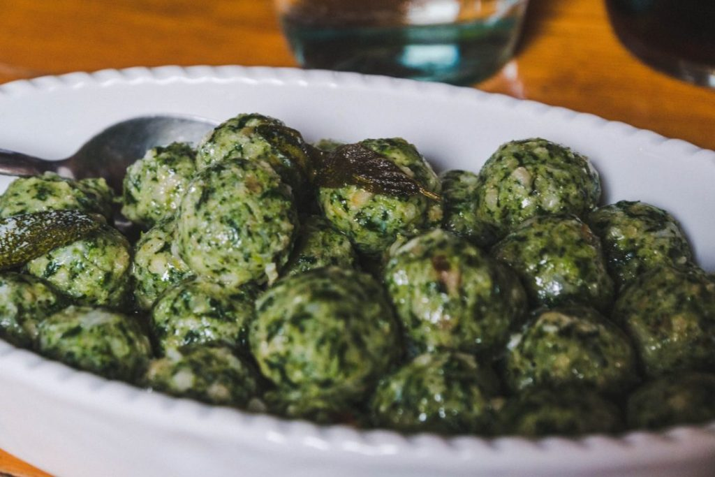 Green strangolapreti dumplings piled high in a white dish, a specialty in in Valle di Ledro, Italy