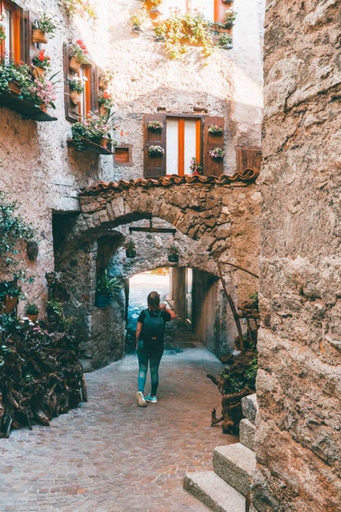 Addie wandering through a stone archway