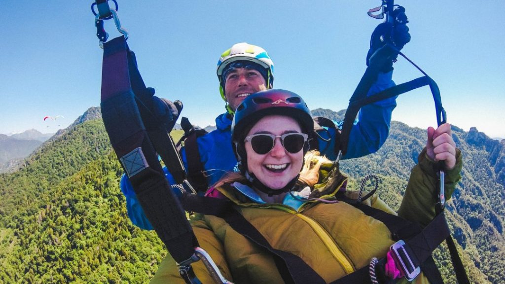 Addie and her paragliding pilot taking a selfie in the air