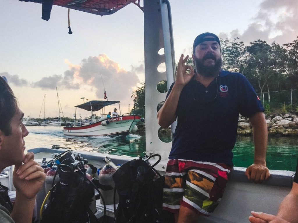 Israel in colorful swim trunks and a scubatony polo, sitting on the edge of the dive boat giving a dive briefing
