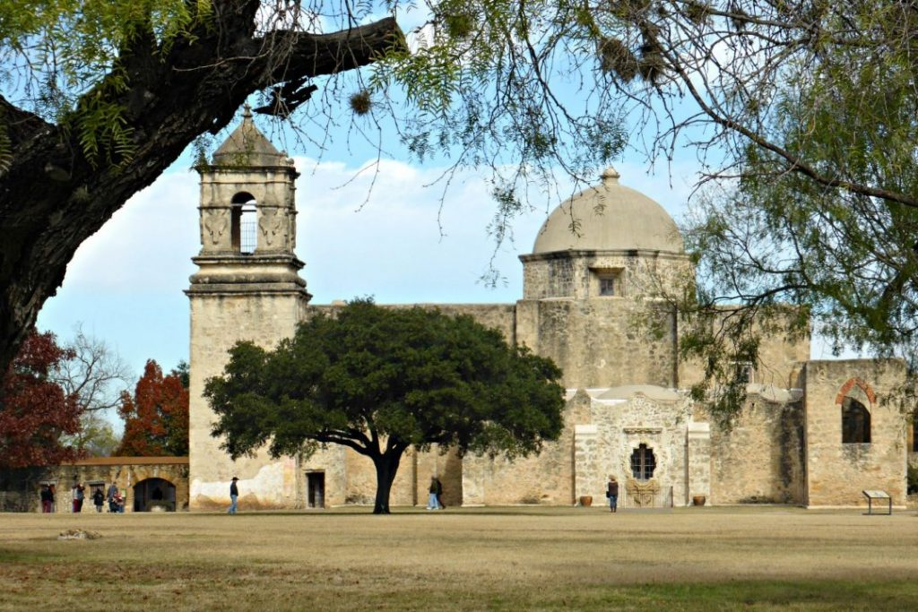 The San Antonio Mission, a light brown brick building with a tower and dome