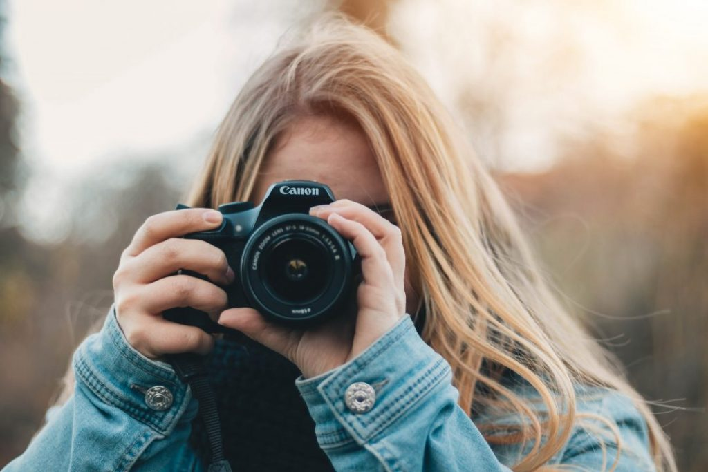 A blonde girl holding a camera up to her eye