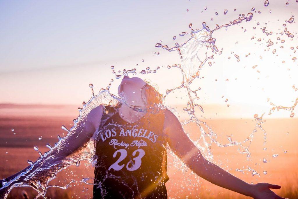 backlit girl splashing water