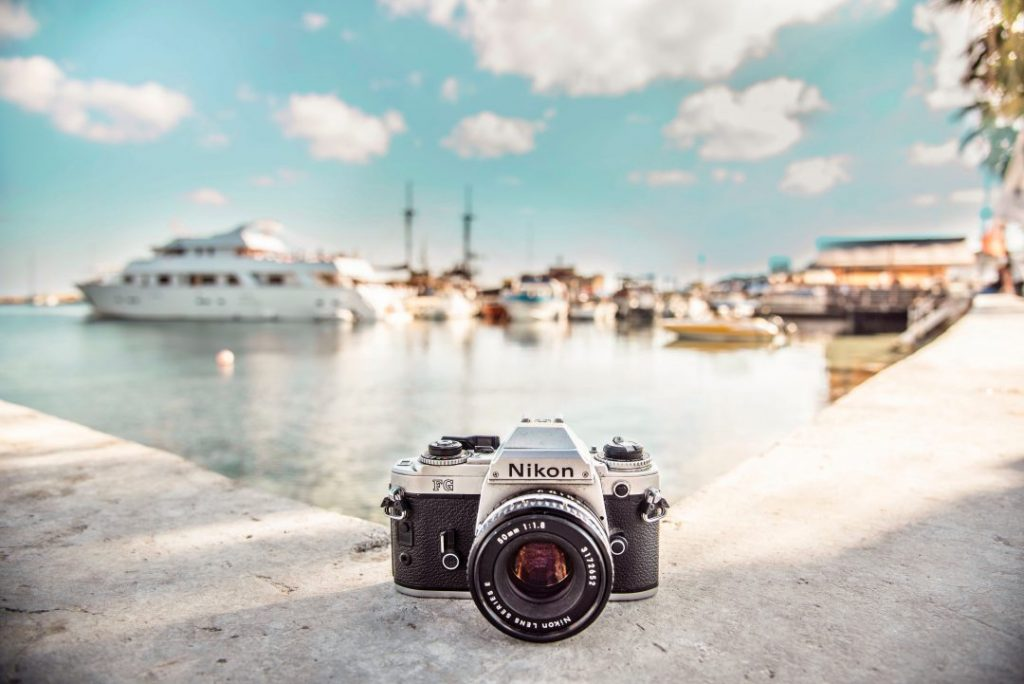 A Nikon camera sitting on the sidewalk by a harbor full of boats