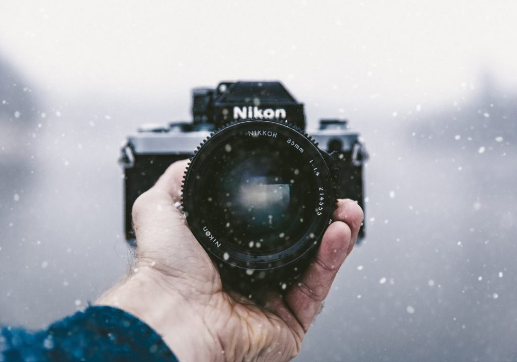 A hand holding a Nikon camera in the snow - how to choose the best camera for travel photography