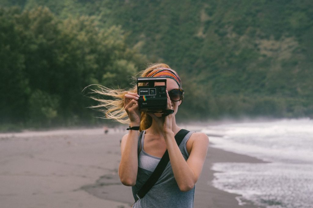 A woman by the ocean, holding a camera up to her face