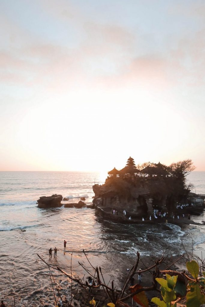 tanah lot temple, perched on a rock in the sea, at sunset