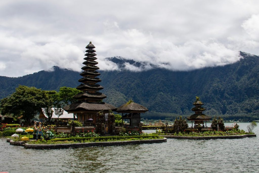 tiered bali temple on a lake with mountains in the background