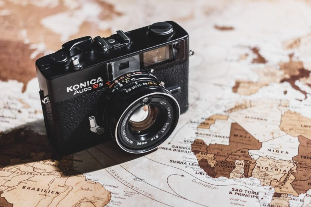 An old Konica camera on a map - how to choose the best camera for travel photography