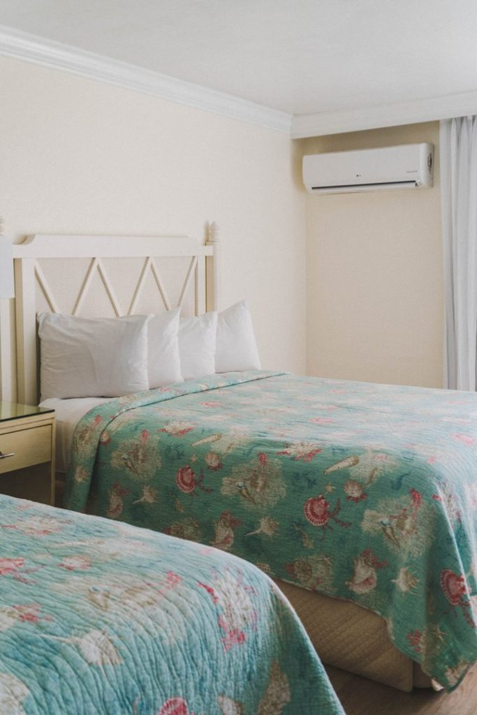 a white bed frame with a blue quilt on top of it