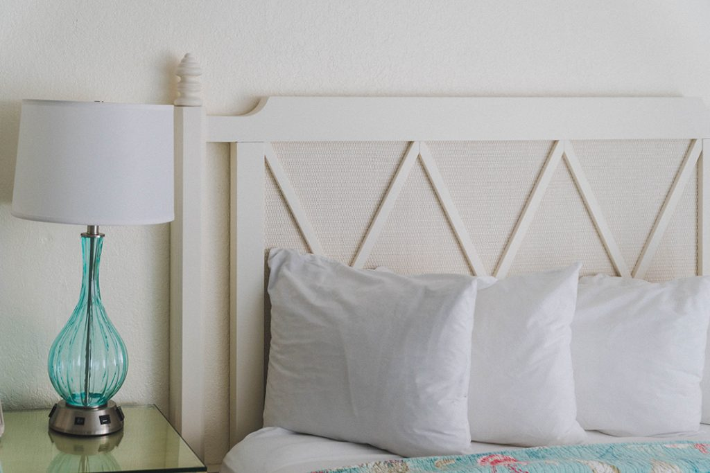 white pillows against a white headboard with a blue lamp on a side table