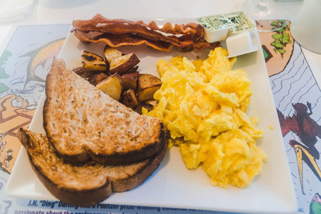 bacon, eggs, toast, and breakfast potatoes on a white plate