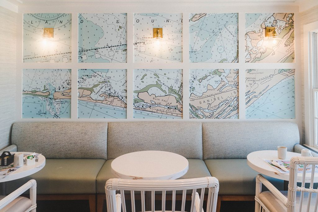 a little nook with a grey couch, white tables and chairs and a blue map of captiva island on the wall