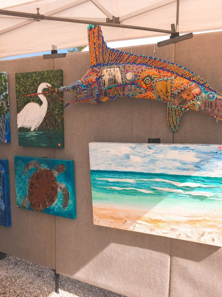 a wall full of paintings of beach and sea animals