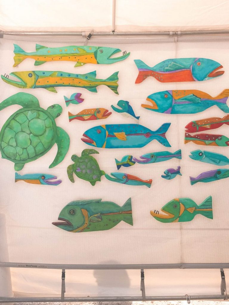 a wall full of paintede wooden sea animals