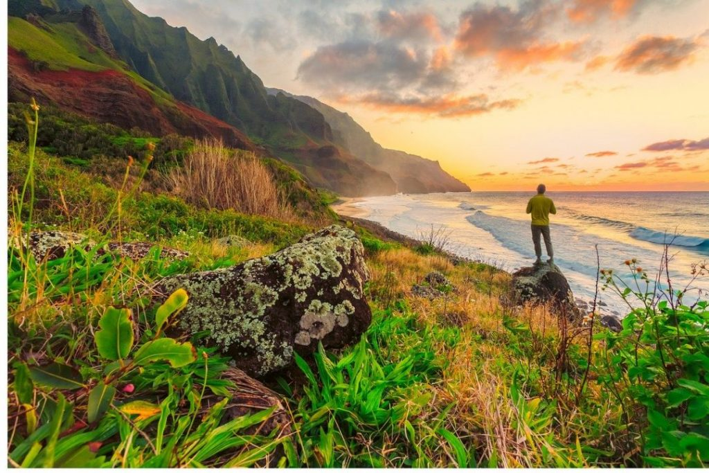 a man standing on a rock in front of a rocky coastline at sunset in Oahu, Hawaii, one of the best spring break destinations in the us