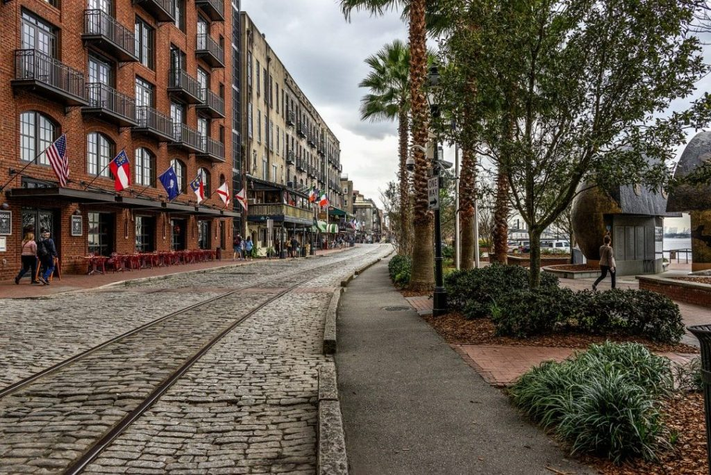 a historic cobblestone road with flags lining the buildings and a railroad track running through the middle