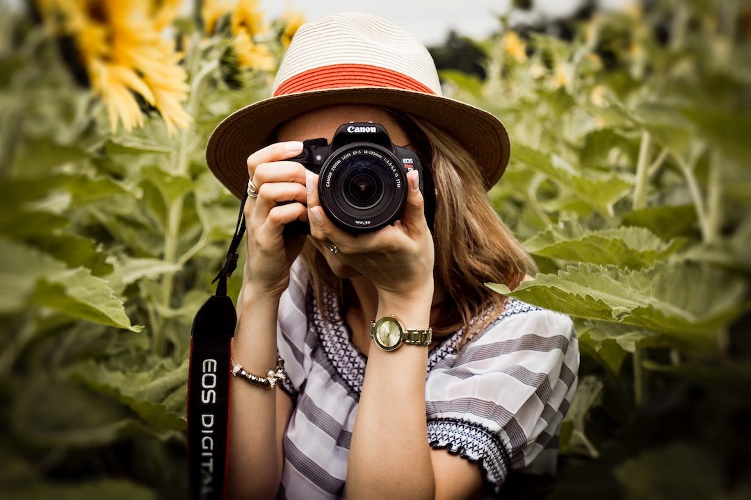 a woman holding a camera in a field of sunflowers