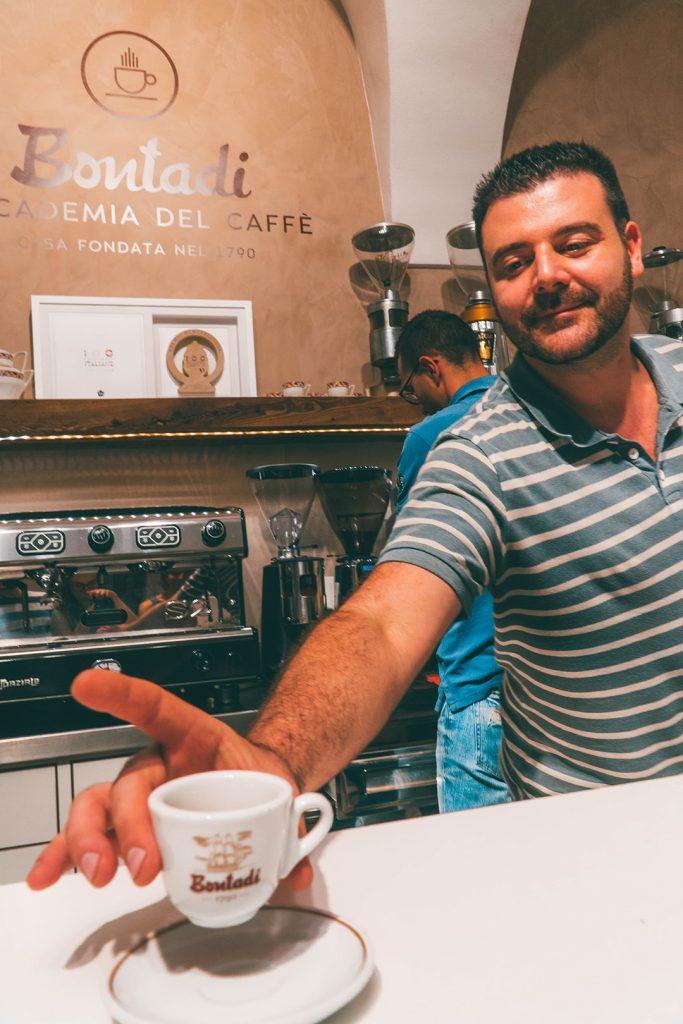 a man handing over an espresso across a bar