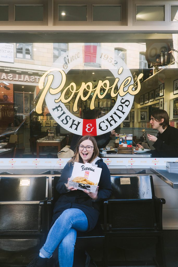 addie sitting on a bench in front of poppie's fish and chips holding a box of fish and chips and looking super excited - a perfect place to stop for food on a girls weekend in london