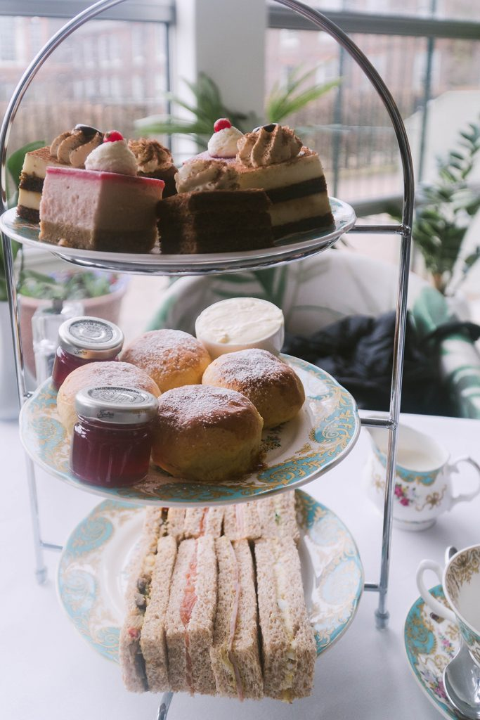 a three-tiered platter of sandwiches, scones, and desserts from afternoon tea at kensington palace - you can't miss this on your girls weekend in london