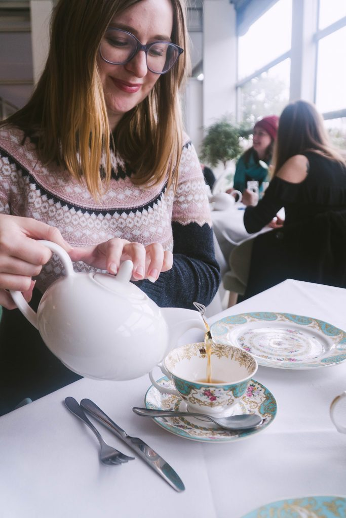 addie pouring tea at afternoon tea at kensington palace