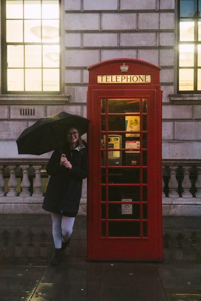 addie standing at a red phone booth holding an umbrella