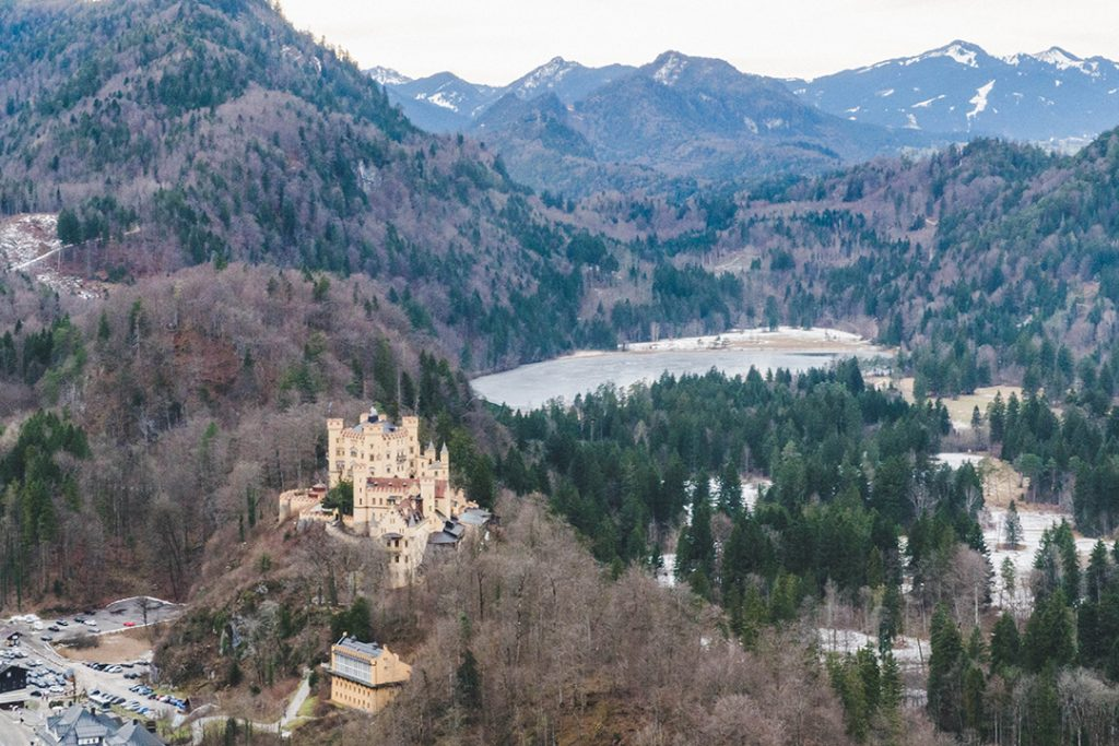 hohenschwangau castle perched on a hill with mountains and a lake in the background