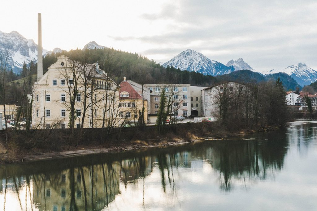 houses along a river in fussen with mountains in the background