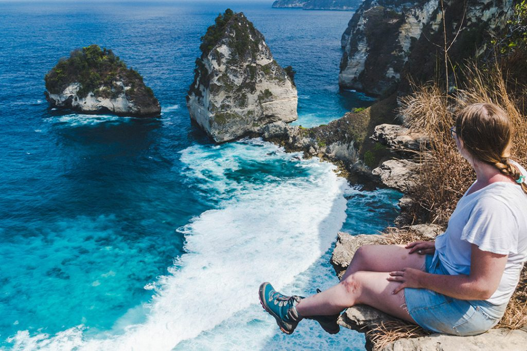 addie sitting on a cliff looking out at diamond beach on nusa penida