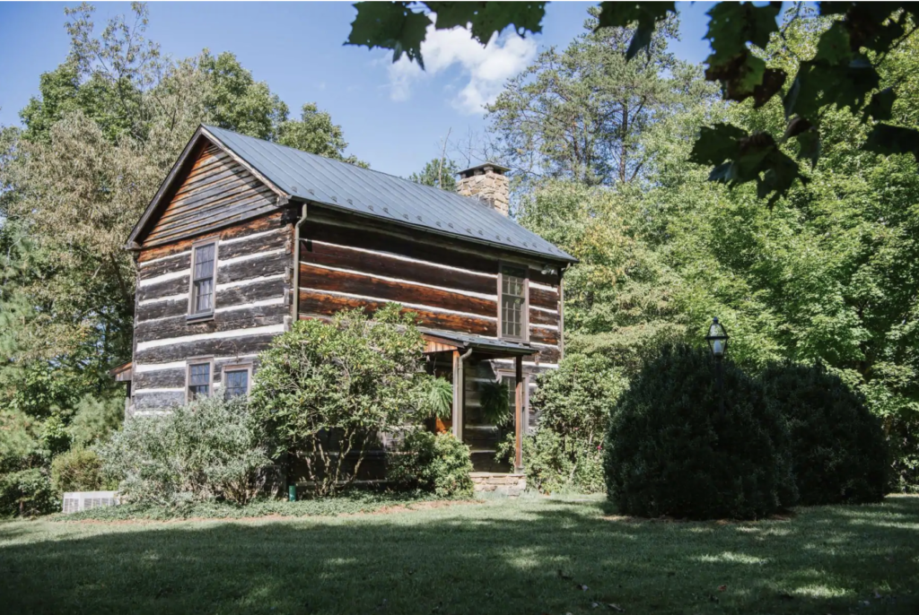 a 2-story log cabin in the woods