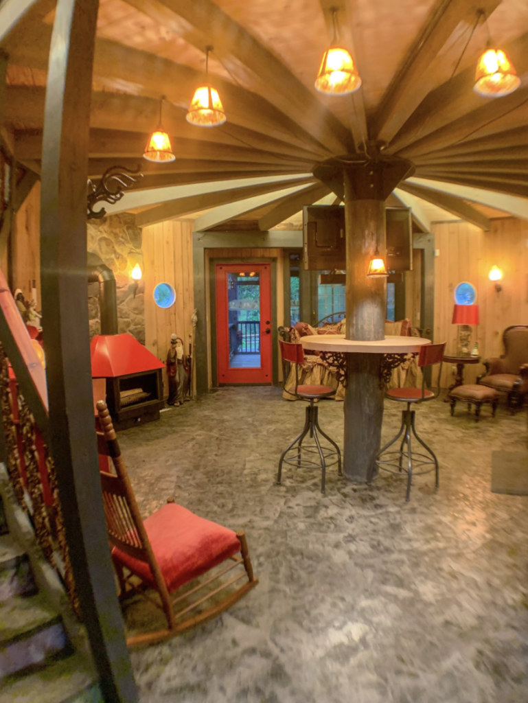 inside the hobbit house, with whimsical furniture in a round room