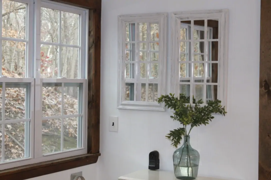 a large vase with stalks of leaves in it next to a window