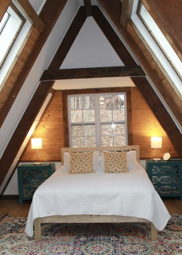 a white bed under a triangular vaulted ceiling