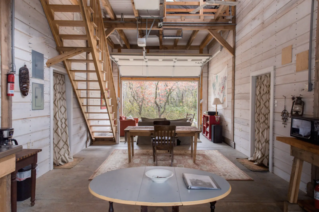 downstairs in the remodeled barn, with a dining room set and wooden stairs leading upstairs
