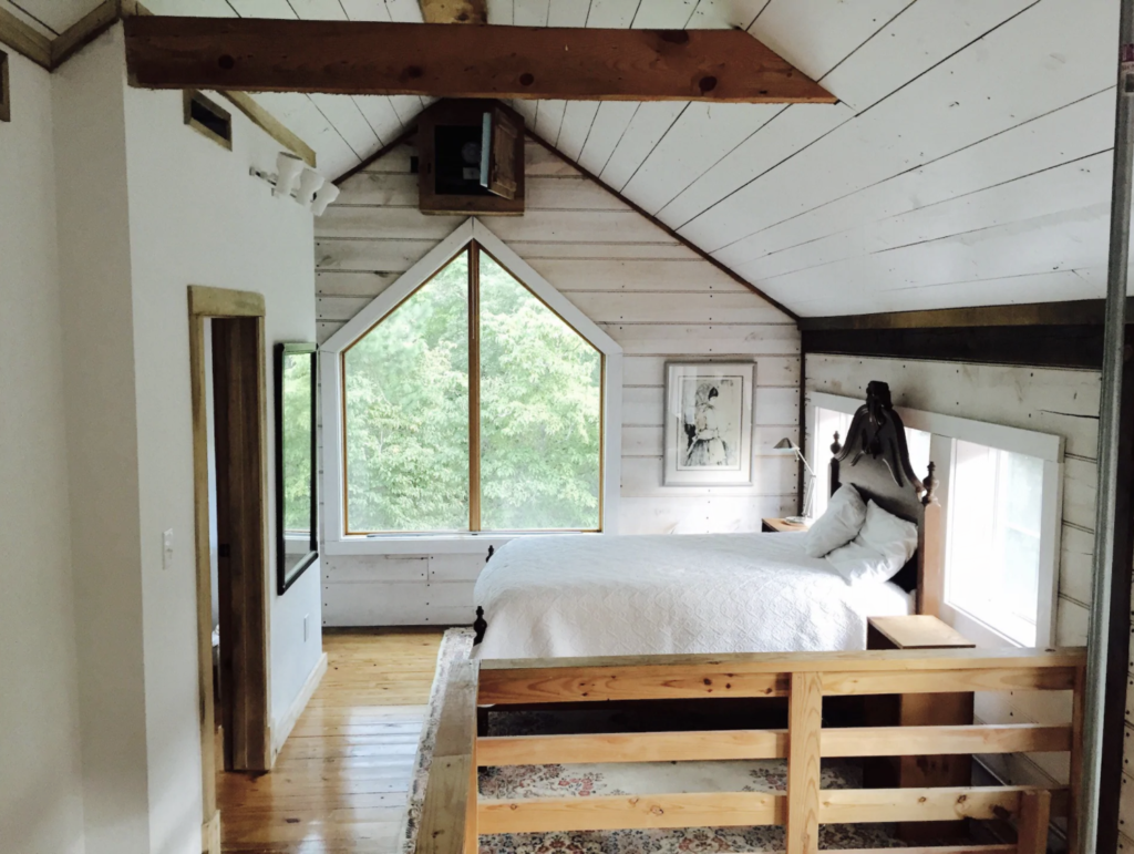 a comfortable looking bed in the loft of a remodeled vintage barn